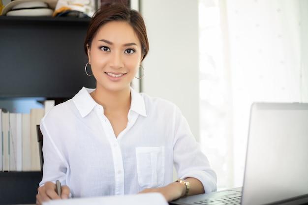 Asiatische geschäftsfrauen, die notizbuch verwenden und für das arbeiten glücklich lächeln