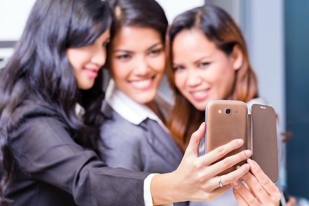 Asiatische geschäftsfrauen, die selfie mit smartphone nehmen