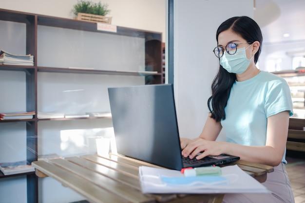 Asiatische geschäftsfrauen, die zu hause arbeiten und medizinische masken tragen asiatische geschäftsfrau in der quarantänezone für coronavirus mit schutzmaske von zu hause aus arbeiten reinigen sie ihre hände mit einem reinigungsgel.