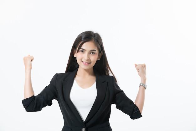 Asiatische geschäftsfrauen lächeln und schlagen herauf handzeichen für das arbeiten glücklich und erfolg und das gewinnen
