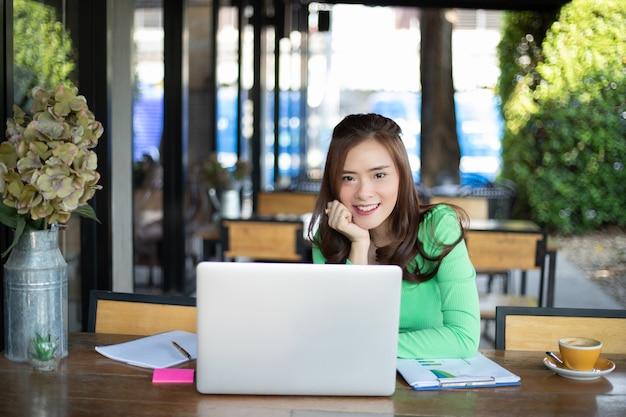 Asiatische geschäftsfrauen lächeln und verwenden notizbuch für analysedokumente und grafisches finanzdiagramm, das arbeitet und sie trinkt kaffee