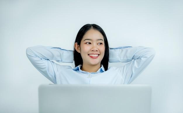 Asiatische geschäftsfrauen sitzen bequem vor einem laptop.