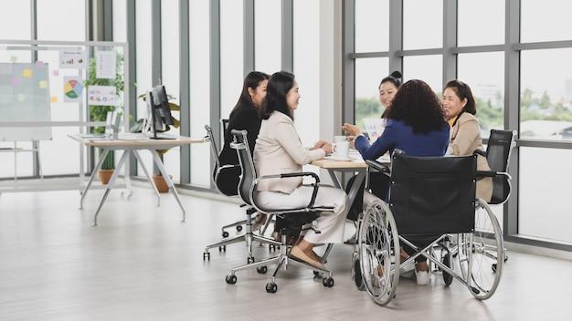 Asiatische geschäftsfrauen und behinderte frauen, die im rollstuhl sitzen, treffen sich auf dem tisch im büro. konzept für geschäftstreffen.