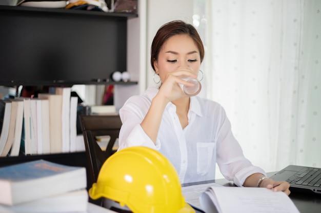 Asiatische geschäftsfrauen und frauen, die unter verwendung des notizbuches für arbeits- und trinkwasser ausführen