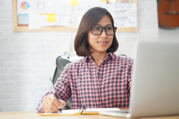 Asiatische geschäftsfraulesung auf laptop-computer mit der prüfung auf netbookpapier