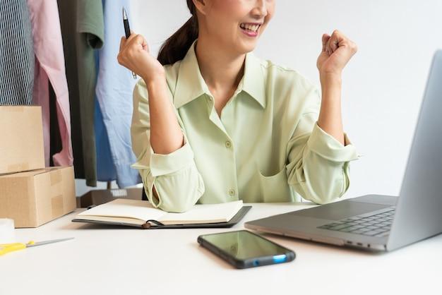 Asiatische geschäftsinhaberin, die zu hause arbeitet und kisten ihres online-shops packt
