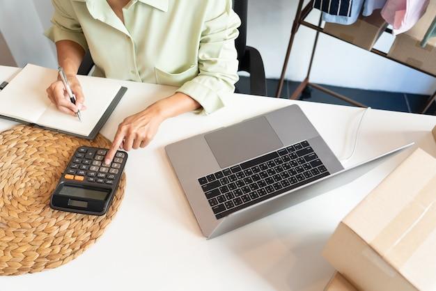 Asiatische geschäftsinhaberin, die zu hause mit der verpackung ihres online-shops arbeitet, bereiten sich darauf vor, produkte an kunden zu liefern, alpha-generation-life-style-konzept.