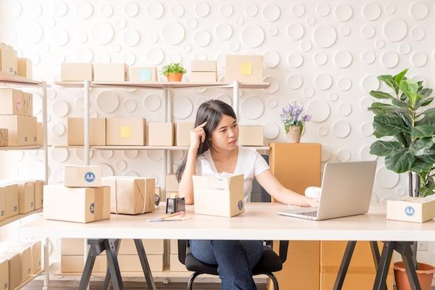 Asiatische geschäftsinhaberin, die zu hause mit packbox am arbeitsplatz arbeitet - online-shopping oder online-verkauf verkaufen