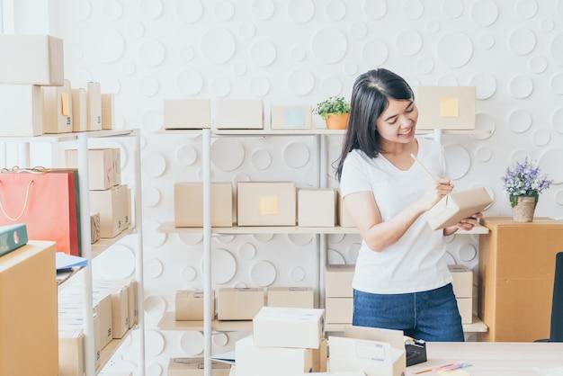 Asiatische geschäftsinhaberin, die zu hause mit packbox am arbeitsplatz arbeitet