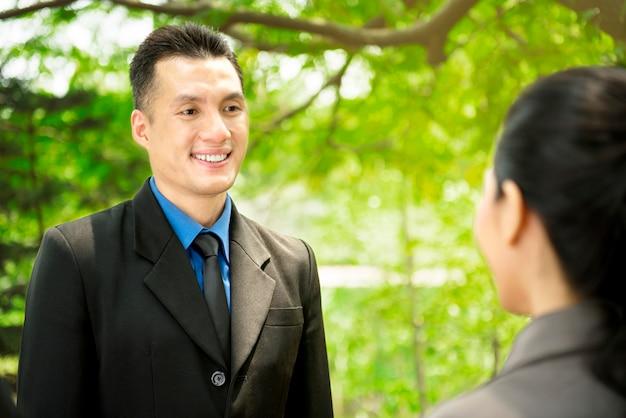 Asiatische geschäftsleute, die arbeitsplan an im freien besprechen