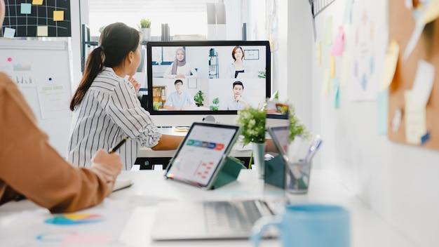 Asiatische geschäftsleute, die desktop verwenden, sprechen mit kollegen, die ein geschäfts-brainstorming über den plan in einem videoanruf-meeting in einem neuen normalen büro diskutieren.
