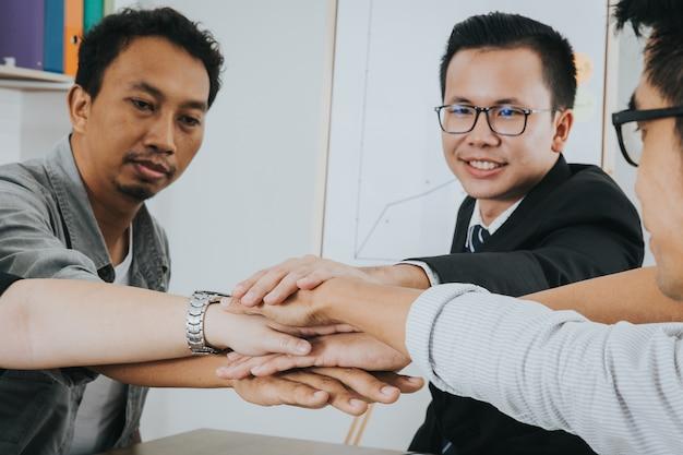 Asiatische geschäftsleute, die ihre hände zusammenfügen. stapel hände