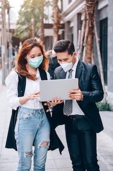 Asiatische geschäftsleute, die im freien arbeiten und den standort für neue unternehmen untersuchen, tragen eine schutzmaske, um grippe und coronavirus covid-19 zu verhindern