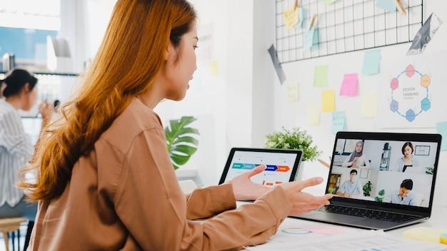 Asiatische geschäftsleute, die laptop verwenden, sprechen mit kollegen, die ein geschäfts-brainstorming über den plan in einem videoanruf-meeting in einem neuen normalen büro diskutieren.