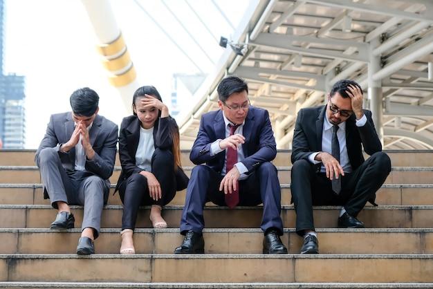 Asiatische geschäftsleute, die wegen arbeitslosigkeit düster sitzen.