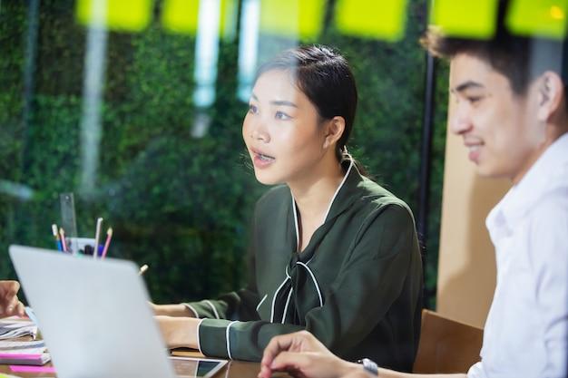 Asiatische geschäftsleute, die zusammen an projekt arbeiten und im büro nachts gedanklich lösen