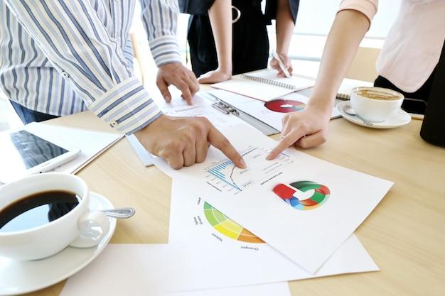Asiatische geschäftsleute gruppieren geschenk und überprüfen finanzmarketingstrategie-unternehmensplan