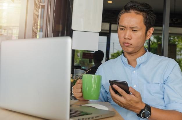 Asiatische geschäftsleute halten ein handy in der hand, schauen sich daten am computer an und sorgen sich um die arbeit