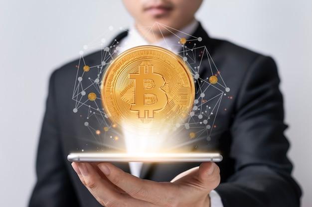 Asiatische geschäftsleute halten ein smartphone, das die welt des virtuellen bitcoin-handels auf weißer wand zeigt
