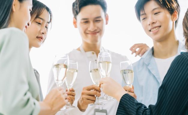 Asiatische geschäftsleute rösten ihre brille und feiern die ergebnisse