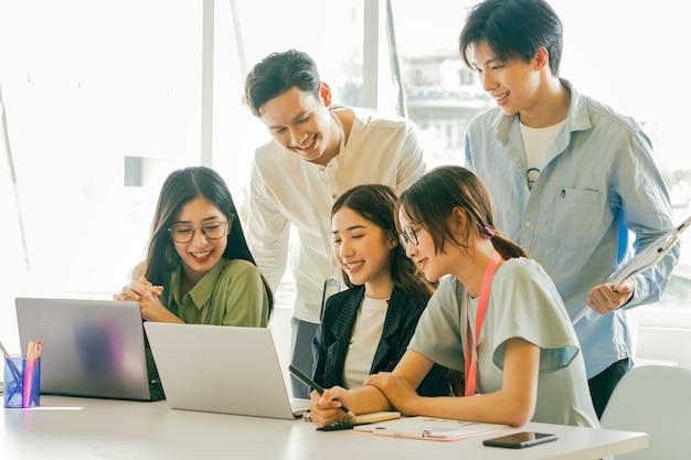 Asiatische geschäftsleute schauen sich gemeinsam auf ihren laptop-bildschirmen ihre geschäftspläne an
