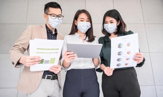 Asiatische geschäftsleute tragen gesichtsmaske diskutieren projekt