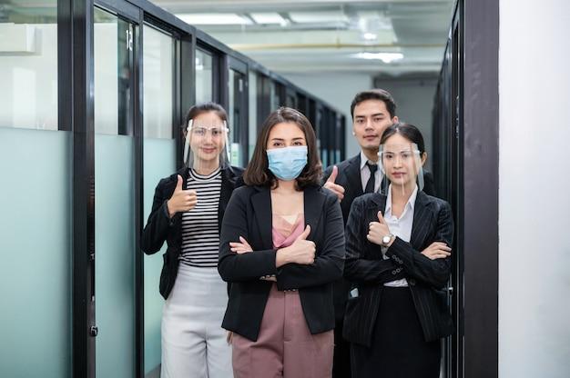 Asiatische geschäftsleute tragen gesichtsmaske, gesichtsschutz mit daumen hoch im wiedereröffneten büro
