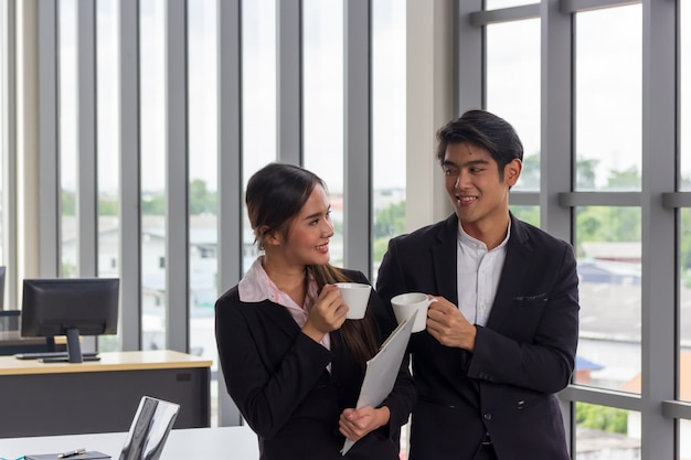 Asiatische geschäftsleute und frauen, die eine weiße kaffeetasse während des bruches im büro halten