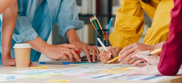 Asiatische geschäftsleute und geschäftsfrauen treffen sich mit brainstorming-ideen über kreative webdesign-planungsanwendungen und entwickeln ein vorlagenlayout für ein mobiltelefonprojekt, das in einem kleinen büro zusammenarbeitet.