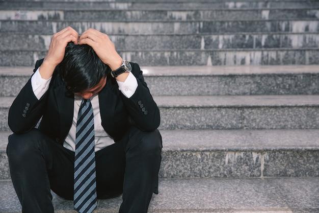 Asiatische geschäftsmänner mit kopfschmerzen oder migräne am rathaus nach der arbeit