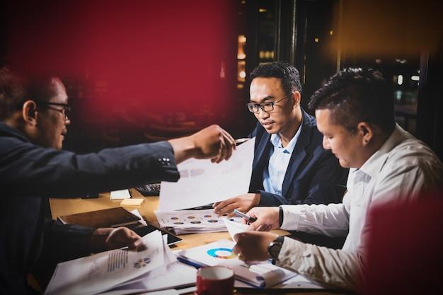 Asiatische geschäftsmänner, welche die arbeit sitzt im bürokonferenzsaal an der nachtszene besprechen