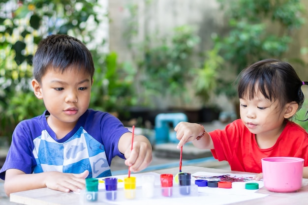 Asiatische geschwisterkinder, die farben auf dem papier im raum zeichnen und malen.