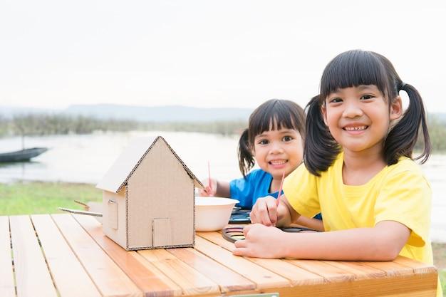 Asiatische geschwisterkinder zeichnen und malen farbe auf dem papier