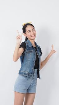 Asiatische geste der jungen frau, die auf weißem hintergrund aufwirft. heiter und selbstbewusst darstellen. zeigen von gesten wie miniherz okay daumen hoch oder darauf hinweisen. glücklich erstaunt aufgeregt und überrascht jacke jeans.