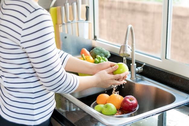 Asiatische gesunde frau, die einen apfel und andere früchte über küchenspüle wäscht und ein obst / gemüse mit wasser reinigt, um das risiko einer kontamination zu beseitigen covid-19.
