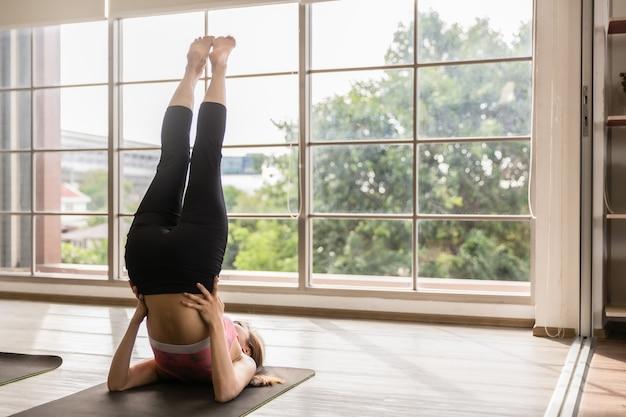 Asiatische gesunde frau, die schulterstand yoga zu hause tut
