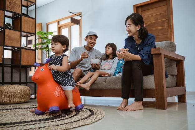 Asiatische glückliche familie, die auf sofa zu hause sitzt und zusammen fernsieht