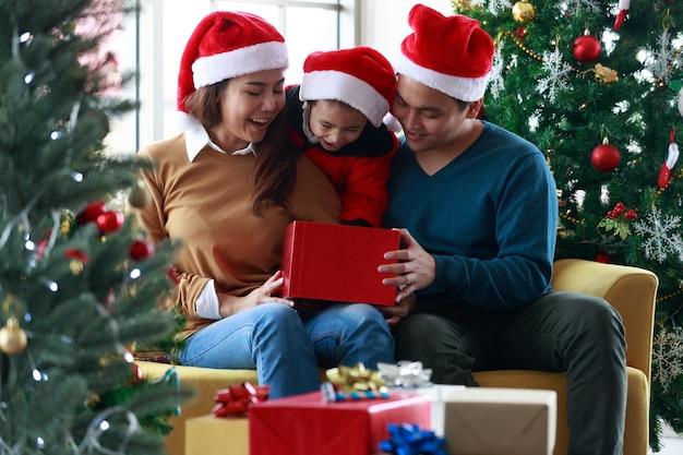 Asiatische glückliche familie und kleines mädchen öffnen magische geschenkbox mit weihnachtsbaum im wohnzimmer, das für das weihnachtsfest dekoriert ist. leute sankt-hüte, die auf der couch sitzen. konzept weihnachtsgeschenkbox.