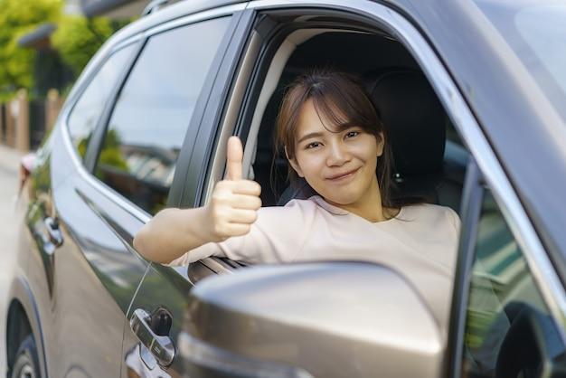 Asiatische glückliche junge schöne frau, die ein auto und daumen hoch fährt
