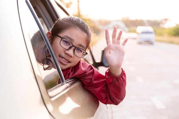 Asiatische glückliche mädchen winken mit der hand, die den kopf aus dem autofenster knallt. urlaub road trip urlaubskonzept.