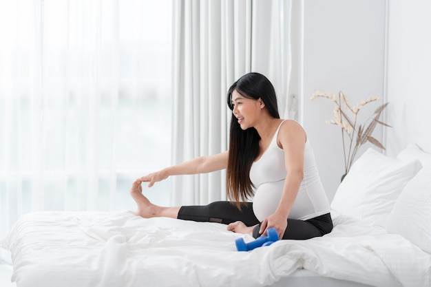 Asiatische glückliche schwangere frau sitzt und trainiert auf dem bett. schwangerschaft, mutterschaft, menschen und erwartungskonzept