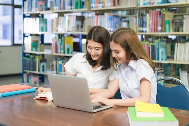 Asiatische glückliche studenten mit der laptop-computer, die in der bibliothek arbeitet und studiert.