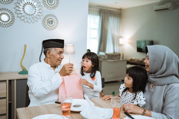 Asiatische großeltern, die enkelkindern während der eid mubarak-feier zu hause ein geschenk machen