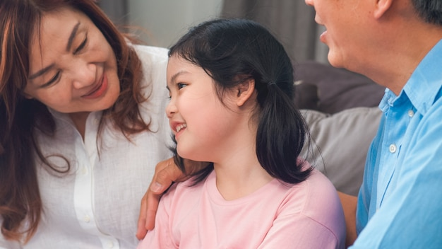 Asiatische großeltern, die zu hause mit enkelin sprechen. der ältere chinese, die alte generation, der großvater und die großmutter, die familienzeit verwenden, entspannen sich mit dem kind des jungen mädchens, das auf sofa im wohnzimmerkonzept liegt.