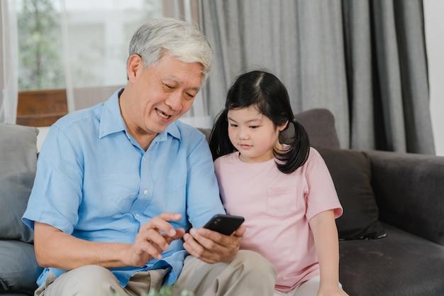 Asiatische großeltern und enkelin, die zu hause handy verwendet. der ältere glückliche chinese, der großvater und das kind verbringen familienzeit mit dem jungen mädchen, das social media überprüft und liegen auf sofa im wohnzimmer.