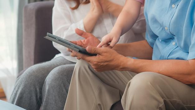 Asiatische großeltern und enkelin, die zu hause tablette verwendet. der ältere glückliche chinese, der großvater und die großmutter verbringen familienzeit mit dem jungen mädchen, das social media überprüft und liegen auf sofa im wohnzimmerkonzept