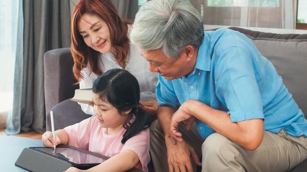 Asiatische großeltern und enkelin videoanruf zu hause. älterer chinese, großvater und großmutter glücklich mit dem mädchen, das den handyvideoanruf spricht mit dem vati und mutter zu hause liegt im wohnzimmer verwendet.