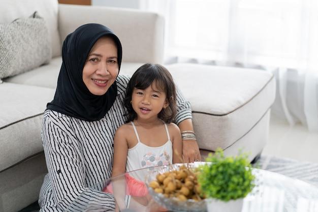 Asiatische großmutter mit enkelin zusammen lächelnd
