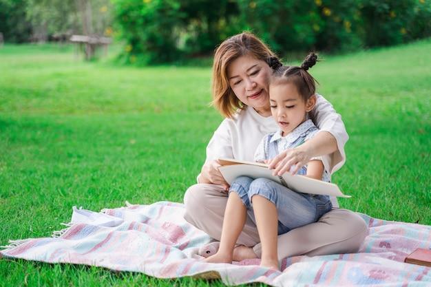 Asiatische großmutter und enkelin, die auf dem feld des grünen glases im freien, familie zusammen genießt picknick am sommertag sitzt