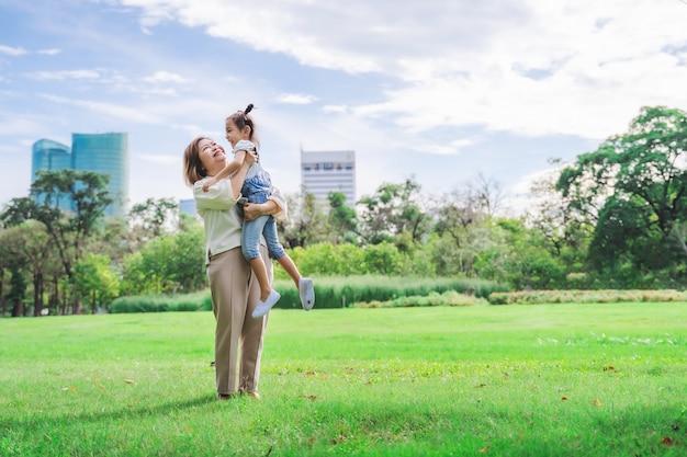 Asiatische großmutter und enkelkinder, die zusammen glückliche zeit im park haben